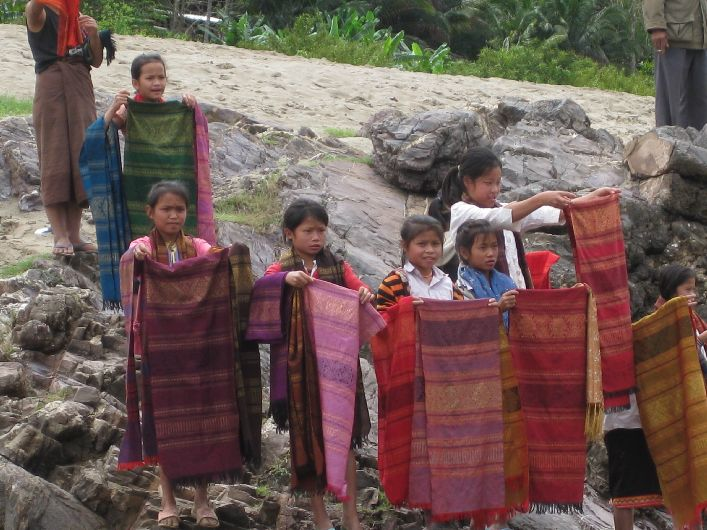 Local children sell sarongs and scarves on the banks of the Mekhong