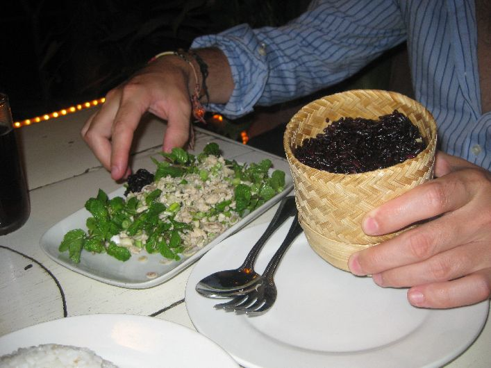 Chicken Laap and black sticky rice. You create a ball of rice by rolling in your palm before scooping up the juicy meat