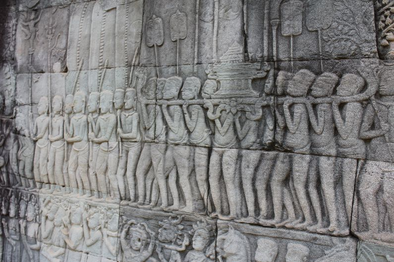 The detailed carvings at The Bayon depict ceremonial scenes
