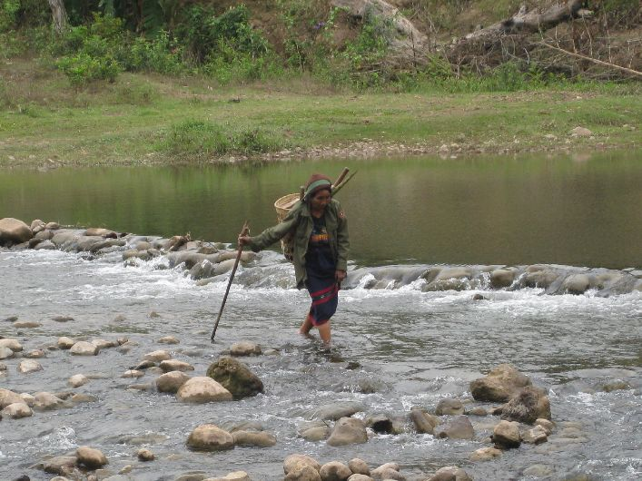 An elderly women carefully crosses a river