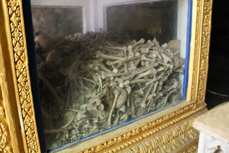 The memorial cabinet in the killing cave with just some of the victims' bones piled up.