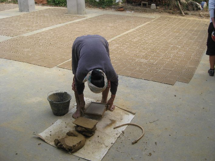 Back-breaking work slicing roof tiles with her feet