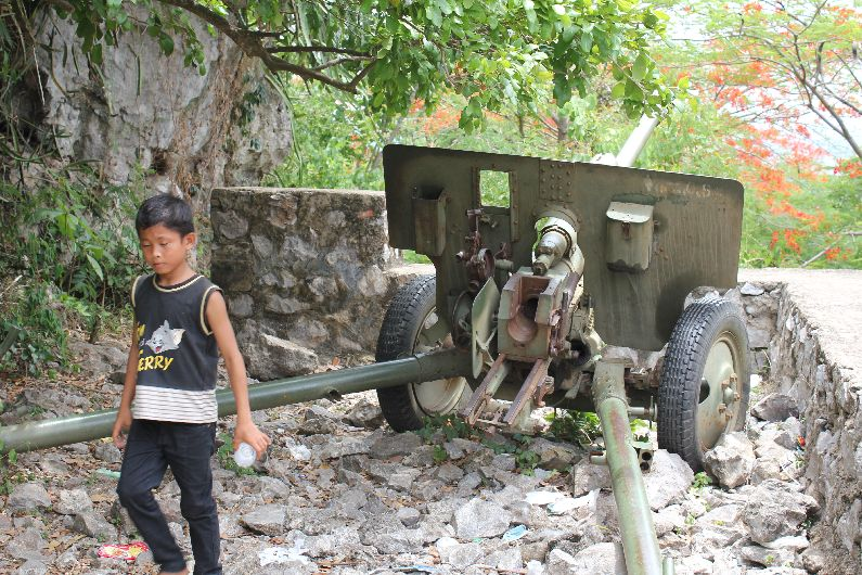 Our young guide shows us the Khmer Rouge artillery near Battambang, Cambodia. The hill is where the Khmer Rouge marched up countless people to murder them, before tumbling them down a hole into a cave. He's collecting empty cans to trade in.